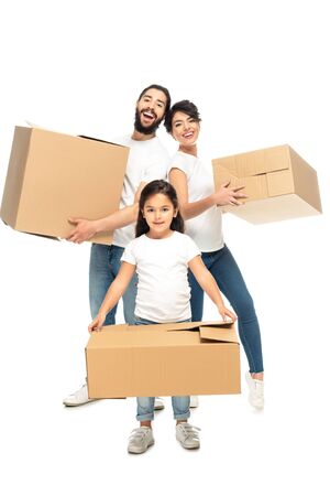 happy latin parents holding boxes and smiling near cute daughter isolated on white