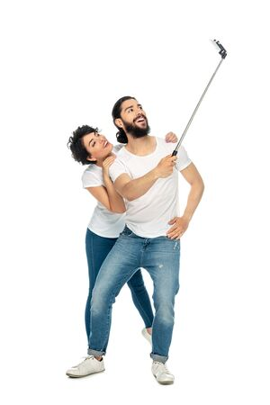 happy latin man smiling near brunette woman while holding selfie stick and taking selfie isolated on white