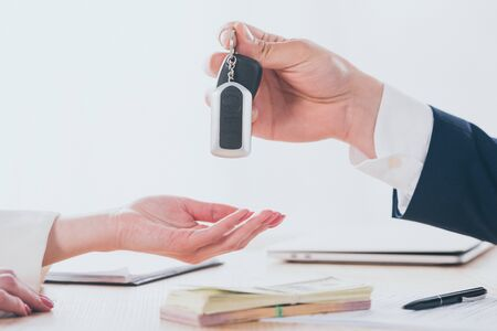 partial view of businessman giving car keys to customer in office