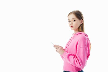 teenage girl in pink hoodie using smartphone and looking at camera isolated on white
