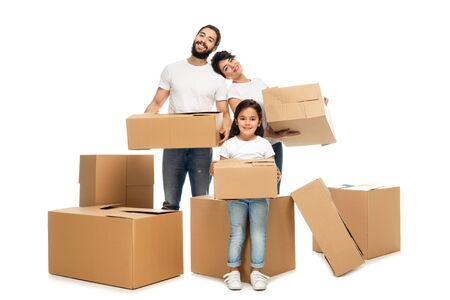 cheerful latin parents holding boxes and standing near cute daughter isolated on white