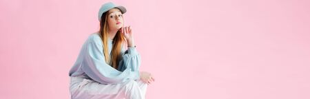 panoramic shot of thoughtful teenage girl in cap isolated on pink Stock Photo