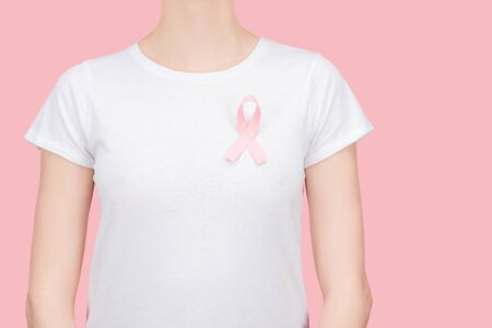 cropped view of woman in white t-shirt with pink cancer sign isolated on pink
