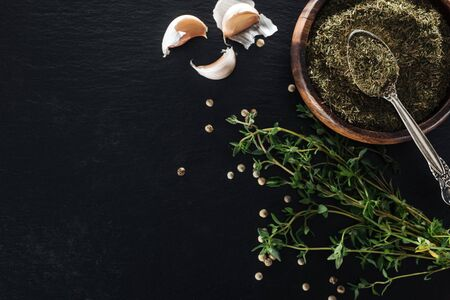 top view of dried thyme in wooden bowl with silver spoon near green herb, white pepper and garlic cloves on black background