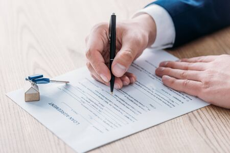 cropped view of realtor writing in loan agreement and car keys on tabletop