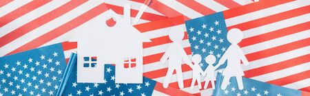 panoramic shot of white paper cut house and family on american flags background Stock Photo