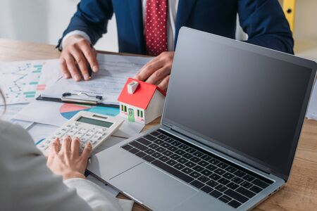 cropped shot of man studying loan agreement and businesswoman using calculator while sitting at workplace with near laptop, house model, graphs and charts Stock Photo