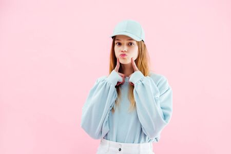 pretty teenage girl in cap grimacing isolated on pink