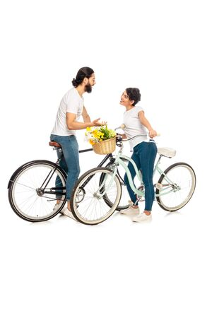 happy latin man talking with attractive brunette woman and standing near bicycle isolated on white Stock Photo
