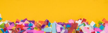 Panoramic shot of multicolored confetti on yellow background