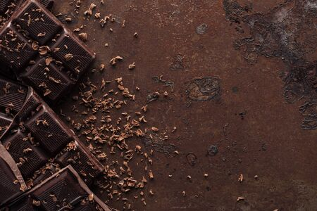 Pieces of chocolate bar with chocolate chips on metal background Archivio Fotografico