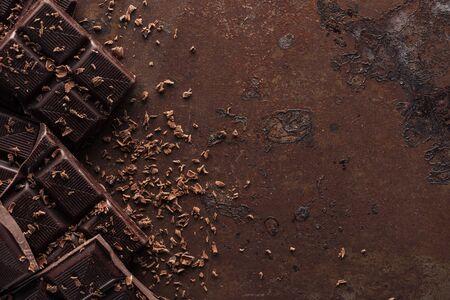 Trozos de barra de chocolate con chispas de chocolate sobre fondo de metal Foto de archivo