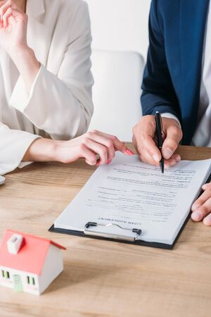 cropped view of man signing loan agreement near businesswoman pointing at signature place