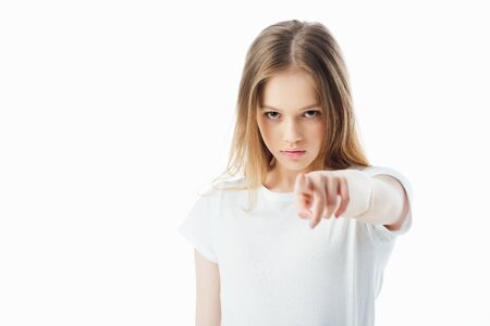 selective focus of offended teenage girl pointing with finger at camera isolated on white