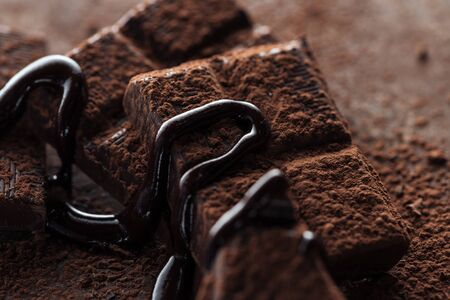 Selective focus of chocolate bar with melted chocolate and cocoa powder