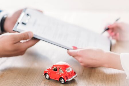 partial view of car dealer giving clipboard to client near miniature car