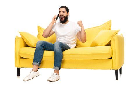happy latin man talking on smartphone and celebrating triumph isolated on white Stock Photo