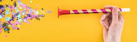 Panoramic shot of woman holding party horn near confetti on yellow background Stock Photo