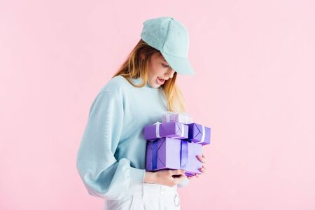 excited pretty teenage girl in cap looking at purple gifts isolated on pink Stock Photo