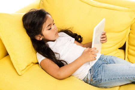 overhead view of cute latin kid lying on yellow sofa and using digital tablet isolated on white