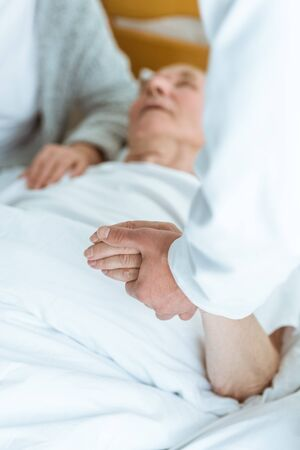 cropped view of doctor standing near patient in coma and holding his hand