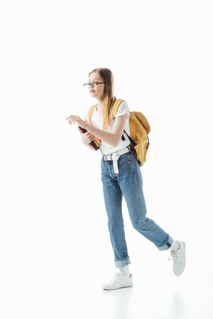 schoolgirl in glasses with backpack holding books and walking isolated on white