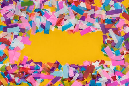 Top view of multicolored confetti frame on yellow background with copy space 写真素材