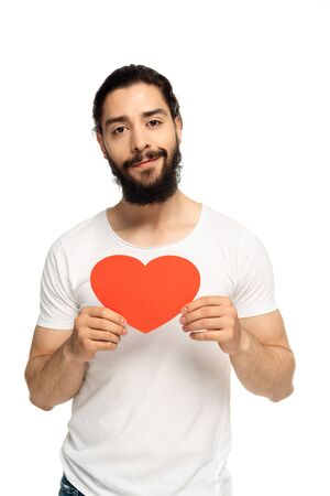 cheerful latin man holding red heart-shape carton isolated on white