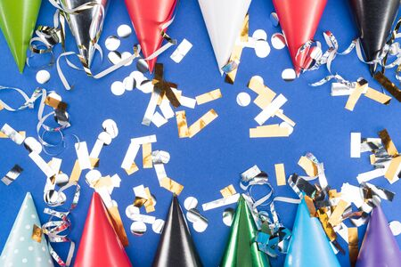 Colorful party hats and silver confetti on blue background