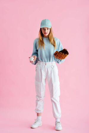 pretty teenage girl in cap holding baseball glove and ball on pink