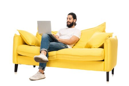 happy bearded latin man in blue jeans sitting in yellow sofa and using laptop isolated on white