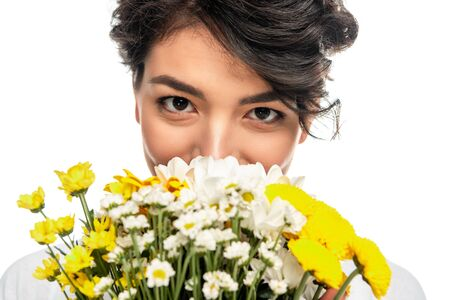 latin woman covering face while smelling flowers isolated on white