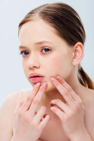 Adolescente bouleversée avec l'acné touchant le visage d'isolement sur le gris Banque d'images