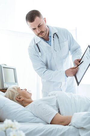doctor with clipboard and sick senior woman lying on bed