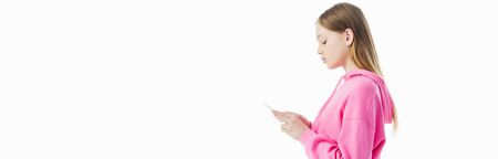 panoramic shot of teenage girl in pink hoodie using smartphone isolated on white, side view