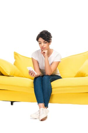 upset latin woman looking at smartphone while sitting on sofa isolated on white Reklamní fotografie
