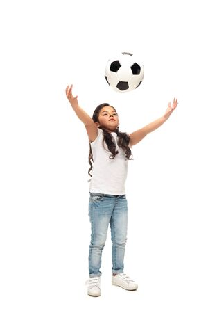 cheerful latin kid playing with soccer ball isolated on white