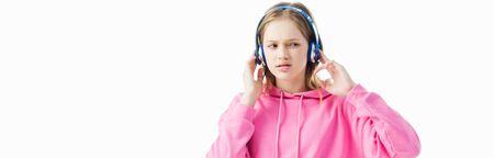 upset teenage girl touching headphones on head isolated on white, panoramic shot