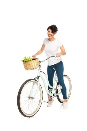 cheerful latin woman riding bicycle and smiling isolated on white