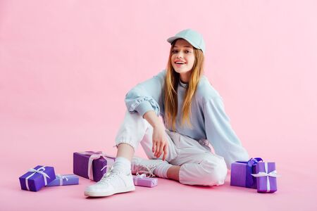 smiling teenage girl sitting near presents on pink