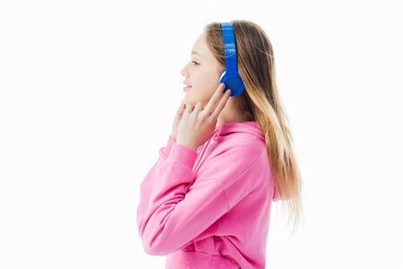 side view of smiling teenage girl touching blue headphones on head isolated on white