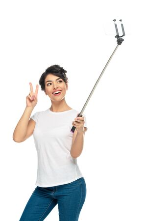 happy latin woman showing peace sign while holding selfie stick and taking selfie isolated on white