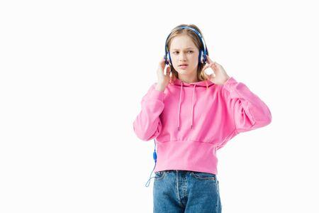 upset teenage girl touching blue headphones isolated on white Stock Photo
