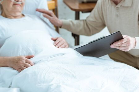cropped view of senior man holding clipboard with sick wife in clinic