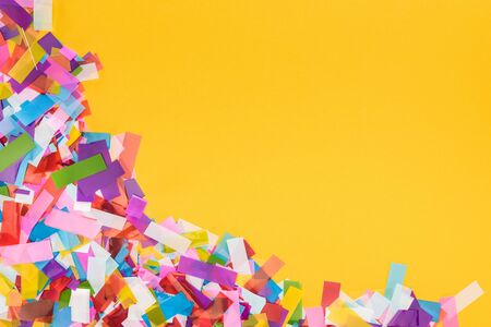 Colorful confetti frame on yellow background