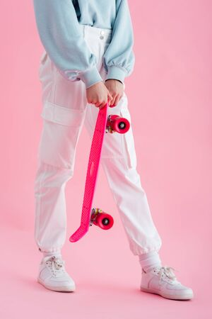 cropped view of teenage girl holding penny board on pink