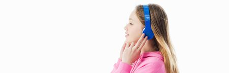 side view of  teenage girl touching headphones on head isolated on white, panoramic shot Stock Photo