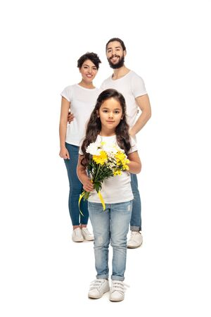 selective focus of cute kid holding flowers near latin parents isolated on white Stock Photo