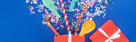Panoramic shot of red gift box, confetti, balloons and party horns on blue background 写真素材