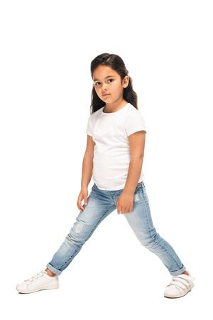 adorable latin child standing in blue jeans isolated on white Stock Photo